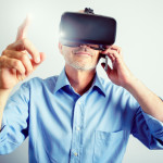 A satisfied mature business man wears a virtual reality headset, controlling the experience with hand gestures, while talking on a mobile/cell phone.